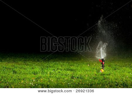 lawn sprinkler spraying water over green grass at night