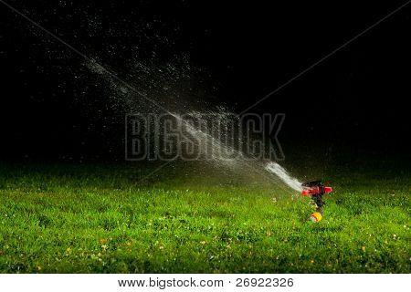 lawn sprinkler spraying water over green grass at night
