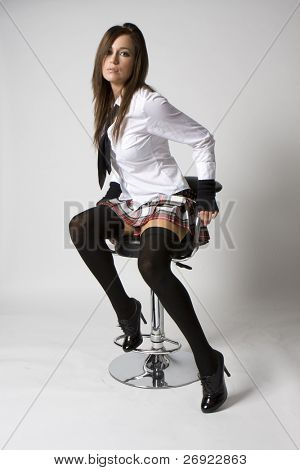 sexy naughty brunette school girl in plaid skirt and black stockings and tie sitting on a nice chair