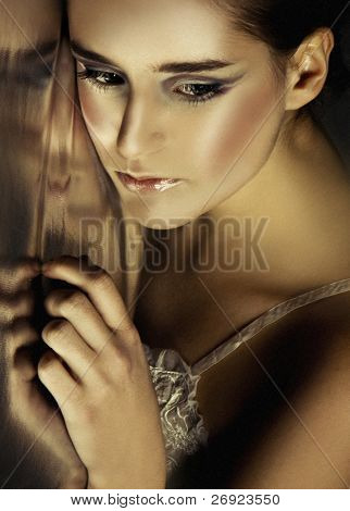 Closeup portrait of a teenage girl leaning against a reflective wall with a pensive expression, golden tone to overall photograph.