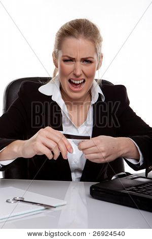Businesswoman Throwing A Tantrum holding her credit card in her hands, seated at desk.