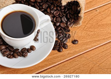 cup with coffee and coffee beans