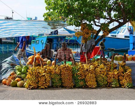 MALE - JULY 1: Three street vendors sit by bananas stall - Market situated on the harbor of Male - capital of Maldives - July 1, 2009 - Male - Maldives.
