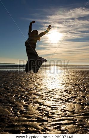 Young woman jumping with raised hands on the beach