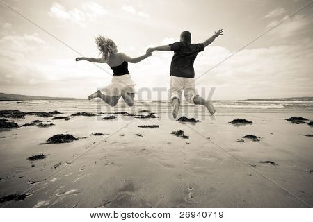 Happiness jump of young couple on the beach