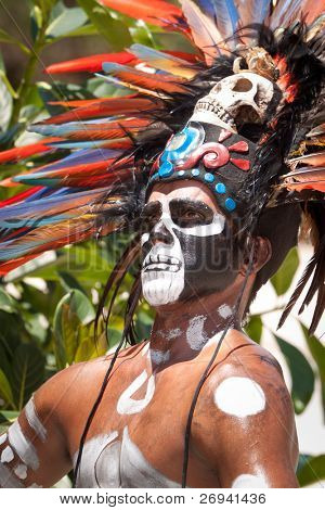 TULUM, MEXICO - JULY 15: Unidentified man in Mayan traditional ornamental feather headdress playing on drums to please the rain god Xipe Totec on July 15, 2011 in Tulum, Quintana Roo, Mexico