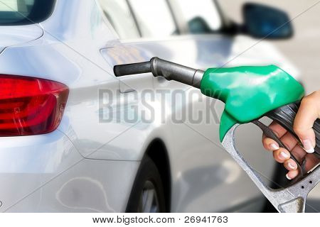 Hand with fuel pistol with new car in background