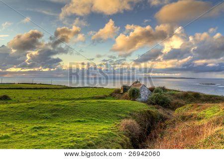 Irish cottage house near the ocean at sunset