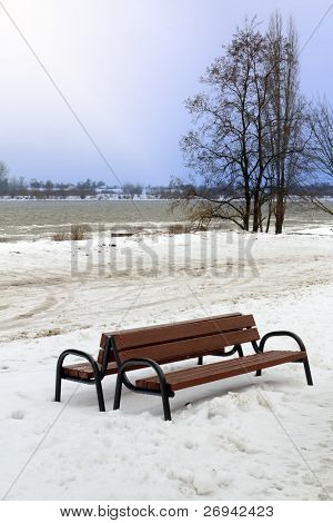 Snowy winter scenery at Wisla river with lonely bench