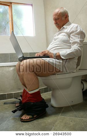 Man working with laptop on toilet seat