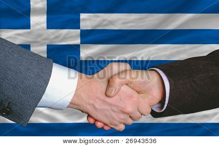 Businessmen Handshake After Good Deal In Front Of Greece Flag
