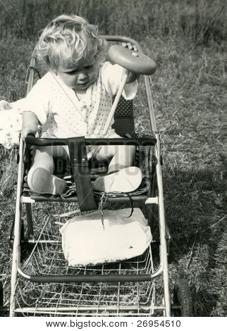 Vintage unretouched photo of little girl plying