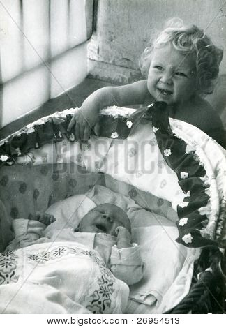 Vintage unretouched photo of little girl with her newborn brother