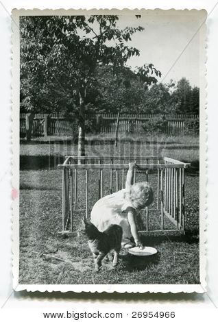 Vintage unretouched photo of young girl feeding cat