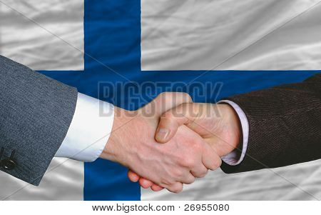 Businessmen Handshake After Good Deal In Front Of Finland Flag