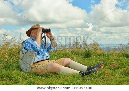 Senior birdwatcher looking by binoculars