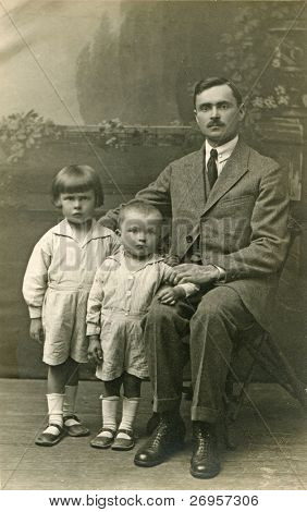 Vintage photo of father with sons (twenties)