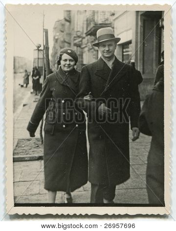 Vintage photo of father and daughter walking on the street (thirties)