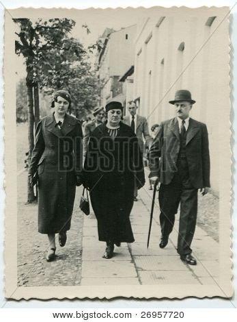 Vintage photo of family walking on the street (thirties)