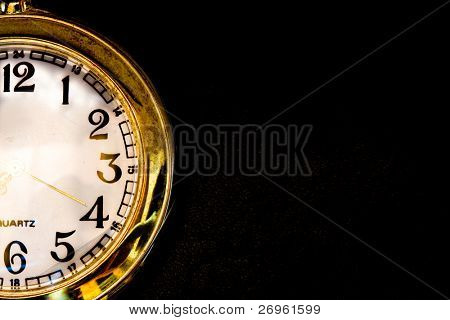 Golden watch macro isolated on black with empty space left for text
