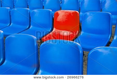 A single red chair in a multitude of blue ones