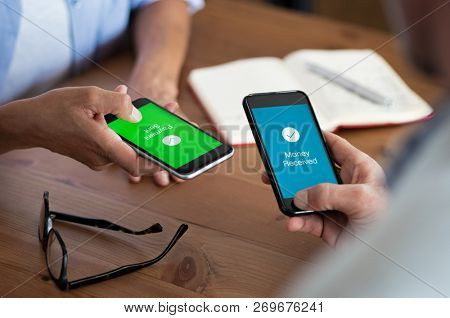 Closeup hands holding mobile phone with application for send and receive  money  Man and woman holdin poster