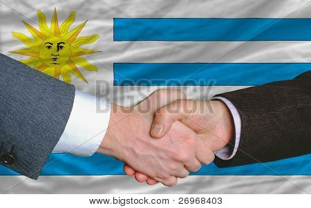 Businessmen Handshake After Good Deal In Front Of Uruguay Flag