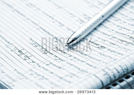 Blue toned image of a silver pen lying on a notebook