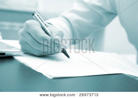 Blue toned image of a businessman writing a document in his office, useful for brochures