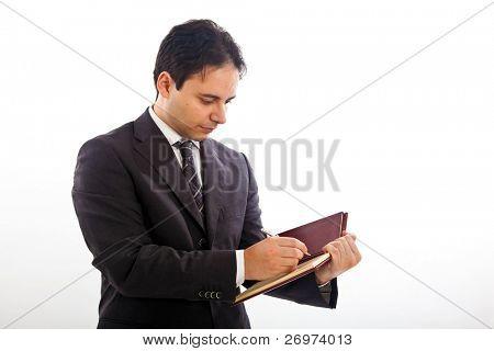 Businessman writing something on his agenda