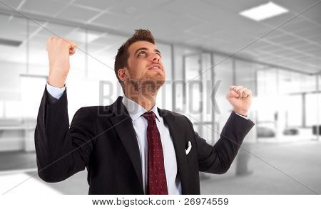 One very happy energetic businessman with his arms raised, in an office environment.