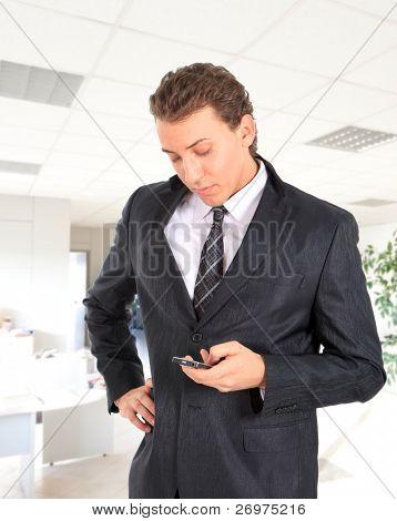 Jovem empresário atraente, escrever uma mensagem de texto em um ambiente de escritório.