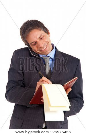 Mature man writing some notes while on the phone
