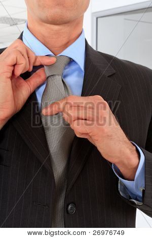 Sophisticated businessman adjusting his tie