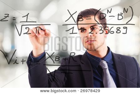 Young business man writing math formulas on the screen