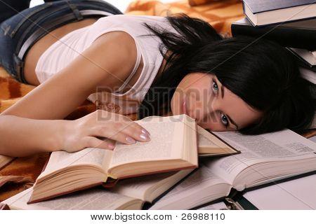 girl lies on open books