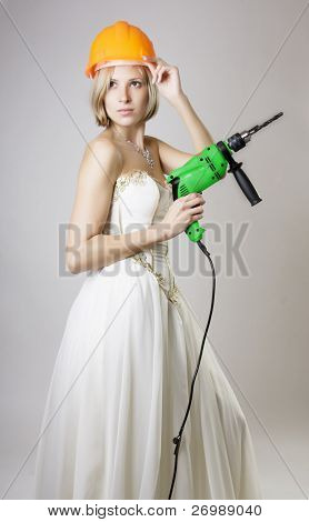 Picture of a girl in evening dress with a drill in the hands of