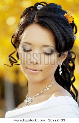 The image of a beautiful bride in the autumn park