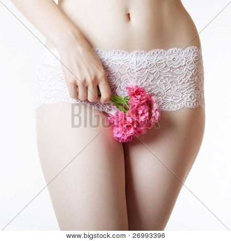 The image of the female abdomen and thighs with a bunch of flowers