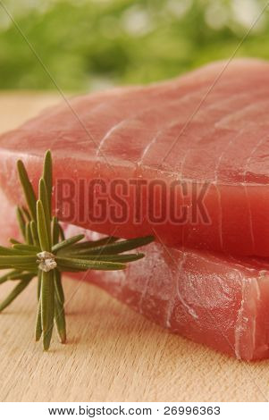 Two tuna steaks and rosemary.