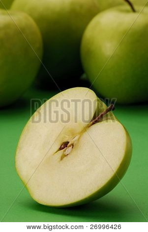 Still life with severalgreen apples and half apple.