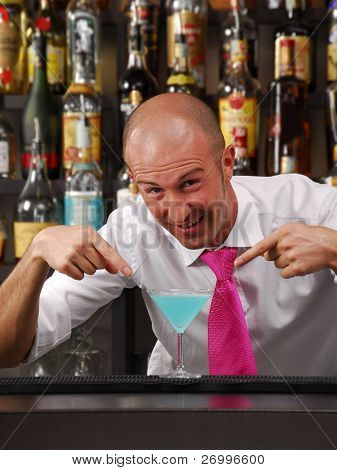 Bartender working. Barkeeping pointing a cocktail. Bantender and cocktail