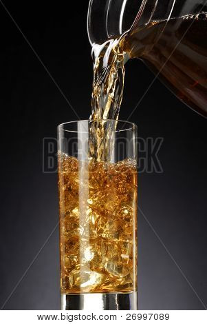 Pouring fresh cold tea on black background.