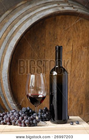 Red wine bottle, cup and grapes on barrels background.