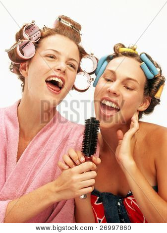 Two funny young women singing with a combs