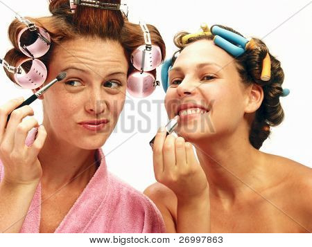 Two funny young women applying makeup mirror