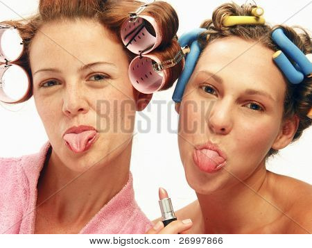 Two funny young women applying makeup mirror and gesturing.