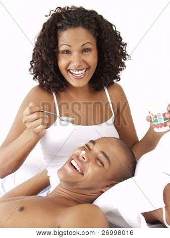 Happy and young afro american couple on bed.