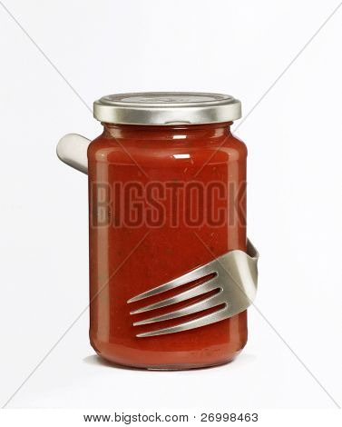 A fork hugging a pot of tomato sauce.