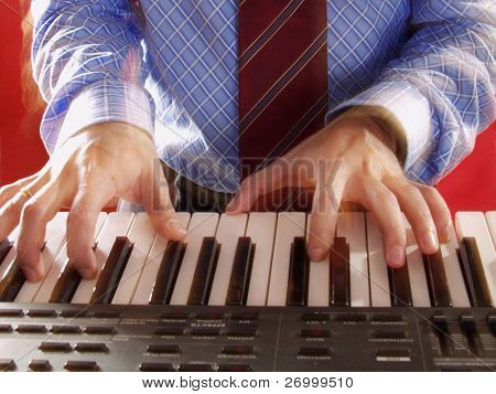Blur hands touching a digital piano keyboard.